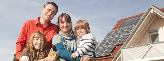 Familie vor Haus mit Solarzellen